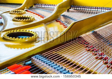 Close up of an antique grand piano showing the sounding board and strings.