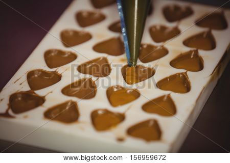 Filling a chocolate mould with a piping bag in factory