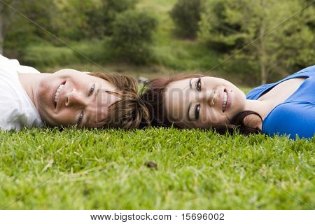 Cute young couple laying in the grass