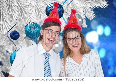 Portrait of happy couple in party hat against digitally generated background during christmas time