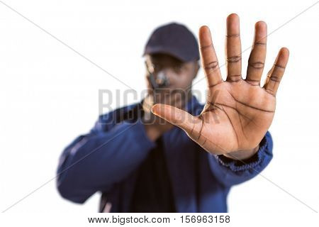 Confident security talking on walkie talkie and making hand stop gesture against white background