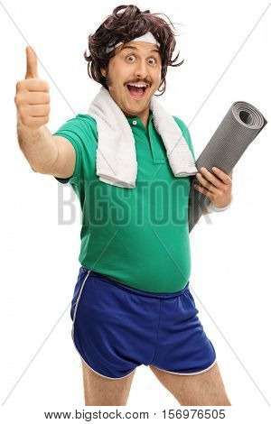Retro sportsman holding an exercising mat and giving a thumb up isolated on white background