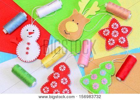 Felt Christmas ornaments. Colorful stuffed felt snowman, reindeer, Christmas tree, flat felt sheets, colored thread, needle. Fun Christmas crafts background. Holiday handmade idea for children