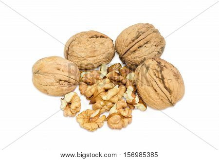 Several whole walnuts in their shell and several shelled kernels of walnuts on a light background closeup