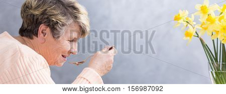 Elderly woman eating with the yellow flowers in front of her