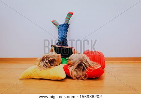 little boy and girl looking at touch pad, home learning