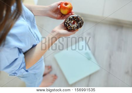 Close up view of woman making choice between apple and donut with blurred scales on background. Dieting concept