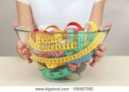 Woman holding bowl with measuring tape on white  background