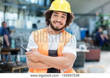 Portrait of confident young manual worker holding walkie-talkie in metal industry