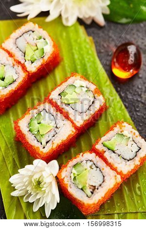 California Maki Sushi with Masago - Roll made of Crab Meat, Avocado, Cucumber, Japanese Mayonnaise inside. Masago (smelt roe) outside. Sushi Food and Natural Flower Concept