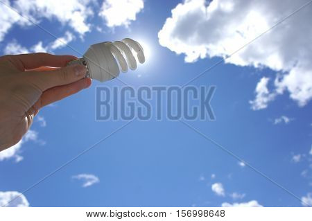 Hand holding a spiral lamp of the sun on sky background. An abstract idea on the topic of electricity of solar energy-saving