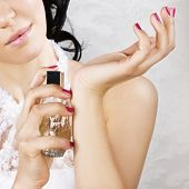 picture of perfume bottles  - Bride spraying perfume on her wrist - JPG