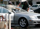 foto of car wash  - Workers at a car wash drying a luxury automobile