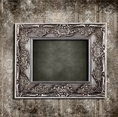 Intricate old frame hanging on grungy vintage wallpaper