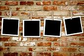picture of wall-stone  - Photos on a clothes line against a grungy brick wall - JPG