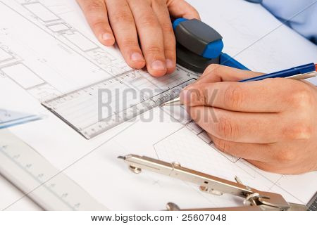 Architect working on architectural plans in the office