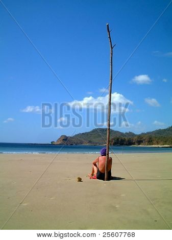 elderly lady sitting on beach against dead tree trunk observing the ocean, san juan del sol, nicaragua.
