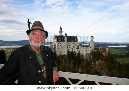 bavarian man in lederhosen posing infront of neuschwanstein castle