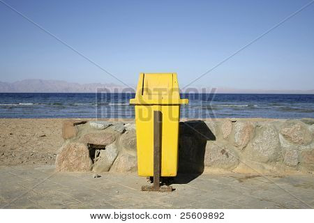yellow dustbin on walkway by seaside