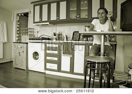 young woman sitting at kitchen bar table smoking