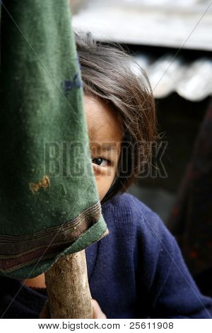 shy little girl hiding behind pole, annapurna, nepal