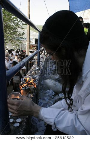 MERON, ISRAEL - MAY 6: Lag Ba'omer pilgrim with beard and payot lights candles during the festivities. May 6, 2007 in Meron.