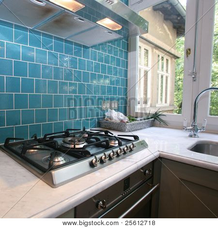 Modern kitchen with turquoise tiles on wall looking onto garden