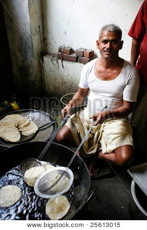 DELHI - FEBRUARY 26: Man cooking chapatis in oil to make Puri on February 26, 2008 in Dehli, India. Chapatis are the staple diet of all Indians.