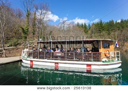 PLITVICE - APRIL 6: Passengers boarding boat to cross lake on April 6, 2010  in Plitvice National Park, Croatia. The park was inscribed on UNESCO World Heritage List in 1979 for it's natural beauty.