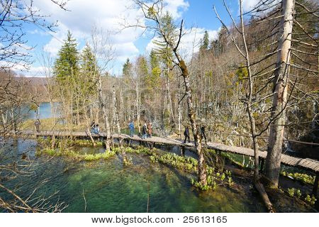 PLITVICE - APRIL 6: Visitors walking along the wooden foot paths on April 6, 2010 in Plitvice National Park, Croatia. The park was inscribed in UNESCO World Heritage in 1979 for it's natural beauty.