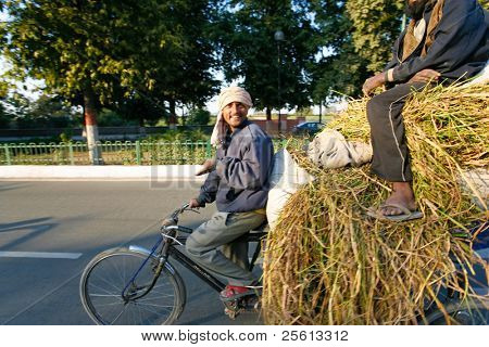 DELHI - FEBRUARY 12: Two men transporting grass using a rickshaw bicycle on February 12, 2008 in Delhi, India. Most Indians cannot afford motorized vehicles.