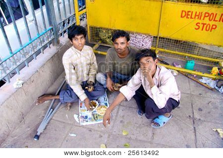 DELHI - SEP 22: Three young street kids eating on ground on September 22, 2007 in Delhi, India. UNHCHR has estimated that India has the largest population of street children in the world.