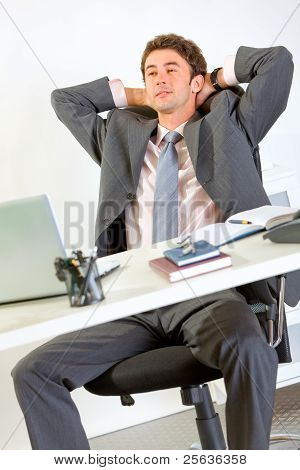 Pleased Modern Businessman Relaxing On Office Armchair