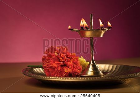Traditional indian lamp and flowers in a plate