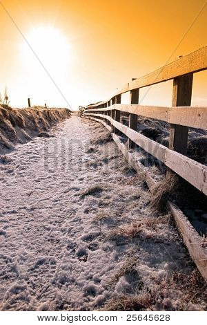 Snow Covered Frozen Path On Cliff Fenced Walk At Sunset