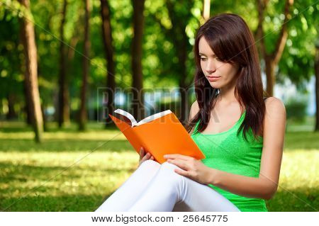 woman reading book at park