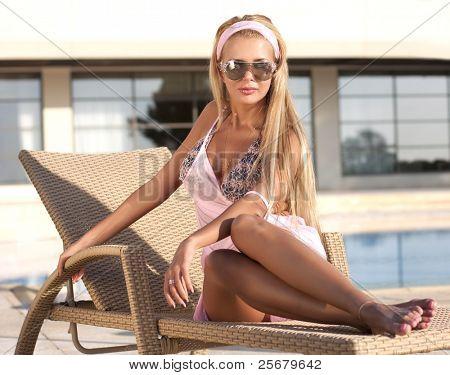 Frau Rosa Badeanzug und dunkle Brille am pool