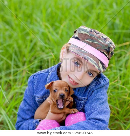 little girl with pet puppy mascot mini pincher in outdoor green grass
