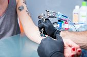 Close-up of the hands of a skilled tattoo artist wearing black gloves while setting a sterile machin poster