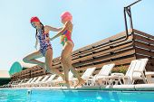 The Portrait Of Happy Smiling Beautiful Teen Girls Jumping At The Swimming Pool. Little Child At Blu poster
