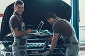 Two Car Mechanics Working In Auto Repair Service. Professional Caucasian Handsome Happy Workers In U poster