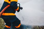 Firefighter Using Extinguisher And Water From Hose For Fire Fighting, Firefighter Spraying High Pres poster