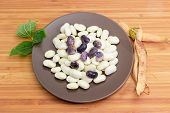 Raw Large White Kidney Beans And Blue-purple Scarlet Beans On Brown Dish With Bean Leaves And Pods O poster