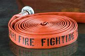 image of firehose  - A rolled up firehose on the wet floor in a firestation used by firefighters - JPG