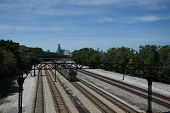 Multiple Railroad Train Tracks Running Parallel With The Chicago Skyline On The Horizon Under A Blue poster