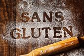 high angle view of a wooden table sprinkled with a gluten free flour where you can read the text san poster
