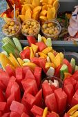 cut and fresh fruit in plastic cups for sale. push carts with cut fruit for sale. poster