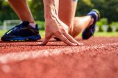 Joint Care For Runners. Hand Of Sportsman On Running Track Low Start Position. Runner Ready To Go Cl poster