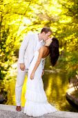 stock photo of married couple  - couple kissing in honeymoon outdoor autumn park - JPG