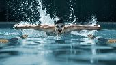 The Dynamic And Fit Swimmer In Cap Breathing Performing The Butterfly Stroke At Pool. The Young Man. poster